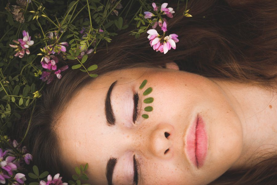 A woman lying on the ground surrounded by flowers and green plants, with tiny leaves arranged like lashes under one eye.