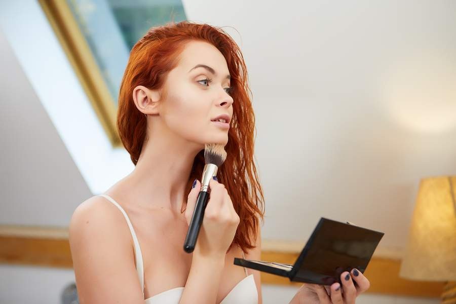 woman using bronzer on fair skin